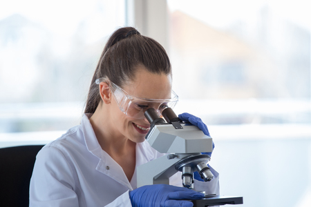 Young pretty woman looking through microscope in laboratory Stock Photo