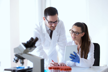 Man and woman scientists looking at tablet and analyzing data from microscope test Stock Photo