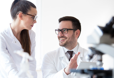 Man and woman scientists analyzing data from microscope test Stock Photo