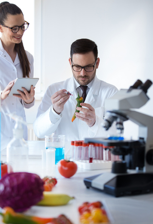 Two scientists working on vegetables with syringe in laboratory