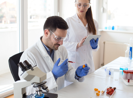 Two scientists working on vegetables testing with syringe in laboratory