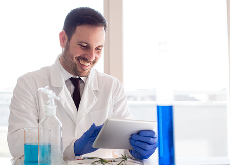 Attractive young man biologist in white coat looking at tablet in laboratory and analyzing seedlings growth