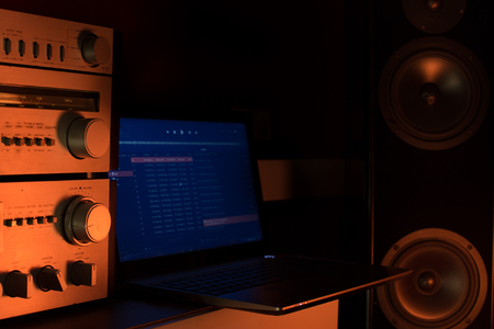 Laptop playing music on big loudspeakers with amplifier. Home sound system concept