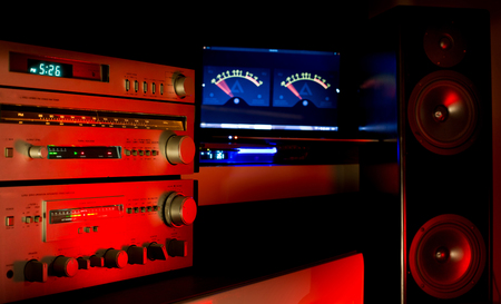 Speakers and amplifier on cozy red lights in dark background. Home sound system concept Reklamní fotografie - 122300059