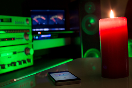Smartphone as remote control for home sound system. Colorful background with speakers and amplifier
