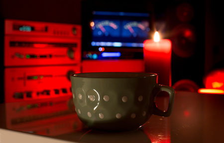Close up of cup of tea with candle on table with big speakers and sound system in background. Music experience in cozy home atmosphere