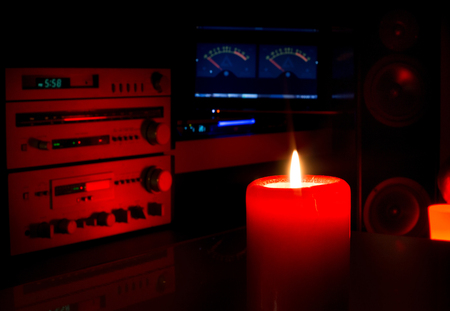 Close up of candle on table with big speakers and sound system in background. Music experience in cozy home atmosphere