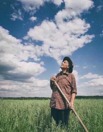 Concepto agrícola y alimentario. Viejo campesino de pie en el campo y mirando hacia el cielo Foto de archivo