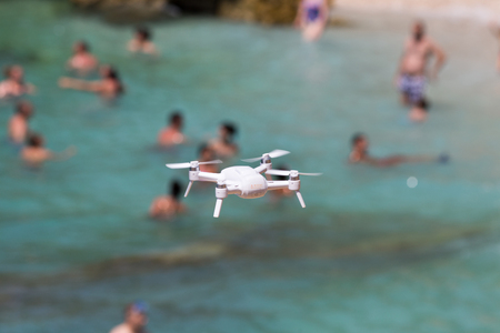 Drone flying above beach. People swimming in background