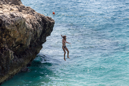 Teenage girl jumping in sea from high cliff. Fun and freedom on summer holiday