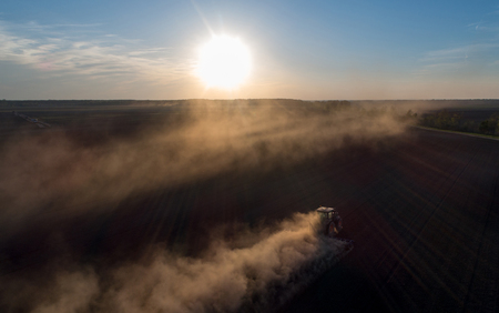 Aerial image of tractor harrowing soil in plains shoot from drone