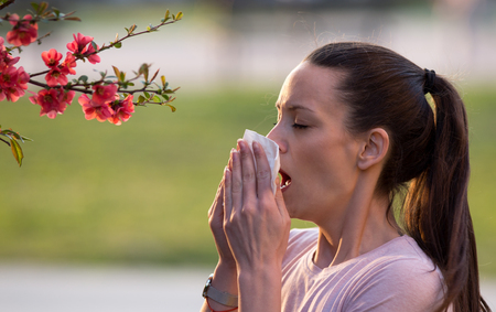Young pretty woman sneezing in front of blooming tree. Spring allergy concept Banco de Imagens