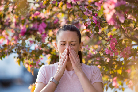 Young pretty woman sneezing in front of blooming tree. Spring allergy concept Stock Photo