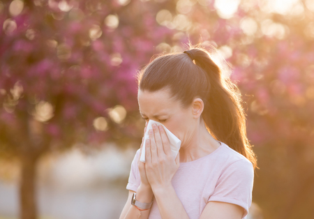 Young pretty woman blowing nose in front of blooming tree. Spring allergy concept