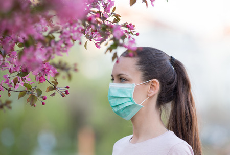 Pretty young woman with mask on face walking beside blooming tree. Spring allergy concept