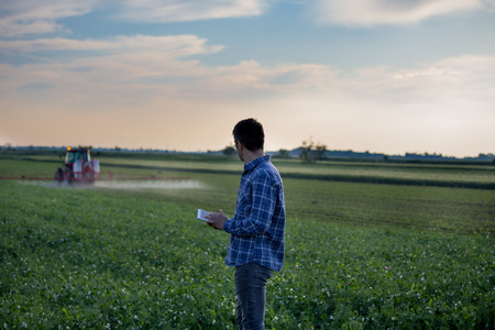 Young attractive farmer with tablet standing in front of tractor in field