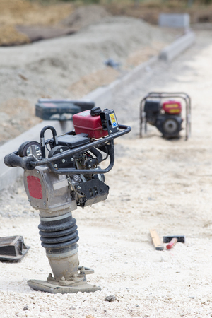 Close up of vibrating plate compactor machine at road construction site