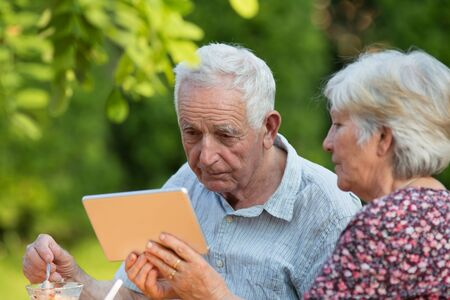 Senior woman showing tablet to  elderly man sitting in park and Stock Photo