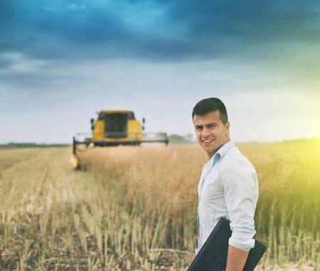 Joven empresario de pie con un portátil delante de la cosechadora en segundo plano. Foto de archivo