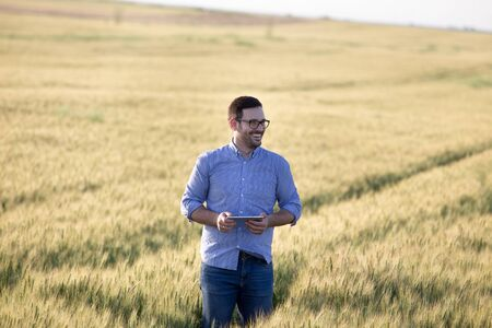 Satisfied young agronomist with tablet standing in ripe barley field in summer