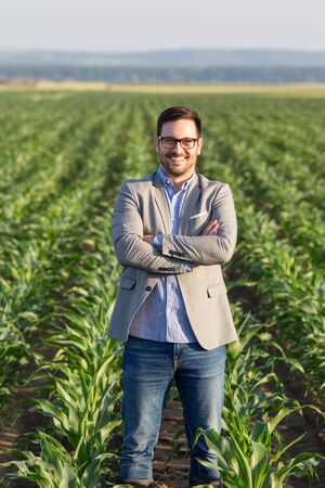 Satisfied businessman with crossed arms standing in corn field in early summer