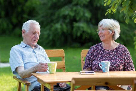 Senior couple sitting at wooden table in garden and drinking tea