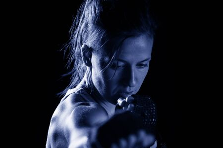 Sportive young woman punching and exercising against black background 版權商用圖片