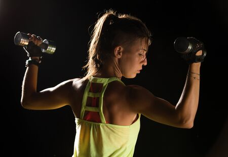 Sportive young woman exercising with dumbbells against black background Stok Fotoğraf