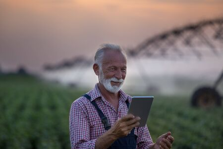 Senior farmer holding tablet in front of  irrigation system in soybean field