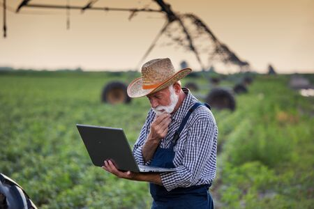 Mature farmer with laptop in soybean field with irrigation system in background