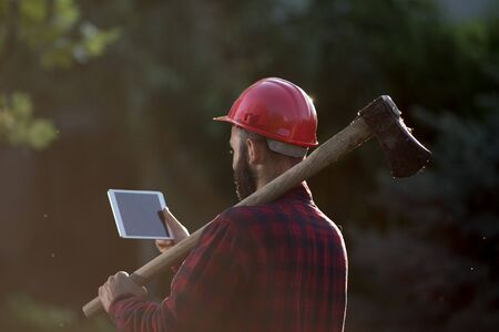 Young lumberjack with beard wearing helmet on head and ax on shoulder in forest and looking at tablet