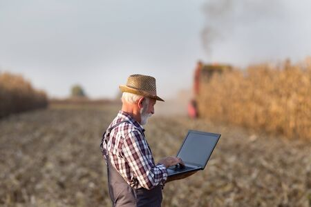 Senior farmer with laptop standing in front of combine harvester in corn field in autumn