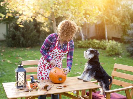 Pretty young woman cutting pumpkin for Halloween in garden while dog making her company