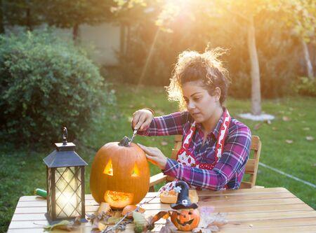 Pretty young woman preparing pumpkin head jack for Halloween in garden