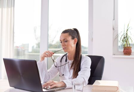 Pretty young woman doctor sitting at desk and looking at laptop in office