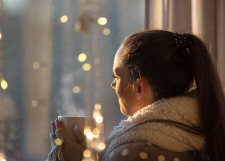 Beautiful girl covered with blanket holding cup of hot coffee with christmas lights in background, Festive moments concept