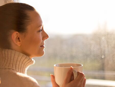 Pretty girl drinking hot coffee beside window at sunrise