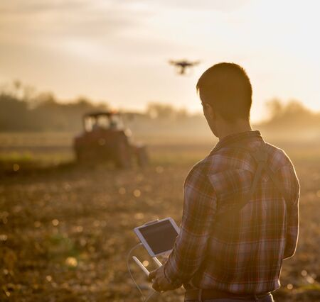 Attractive farmer navigating drone above farmland with tractor in background. High technology innovations for increasing productivity in agriculture