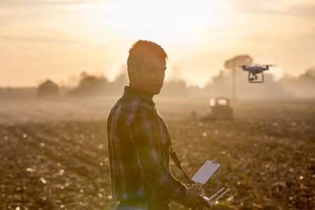 Attractive farmer navigating drone above farmland with tractor in background. High technology innovations for increasing productivity in agriculture Stock fotó