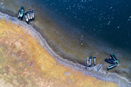 Top view of groups of fishing boats on river coast in winter sunny morning shoot from drone