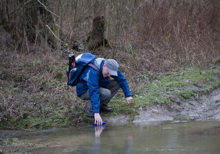 Man picking water from river for drinking in forest in winter