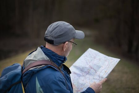 Mature hiker taking break and looking at map iin forest