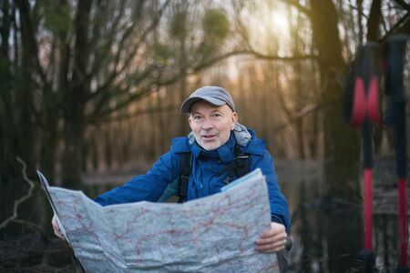 Mature hiker taking break and looking at map in forest