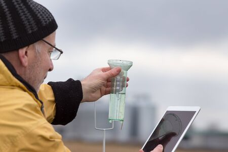 Senior farmer with tablet squatting beside rain gauge in field
