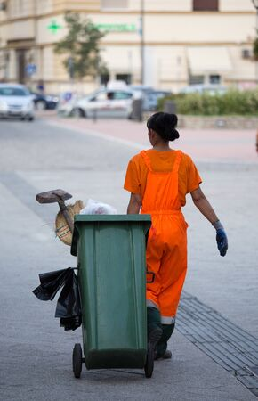Rear view of woman garbage worker in orange uniform pulling trash can with other equipment Standard-Bild