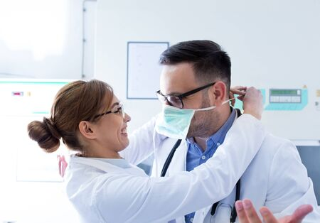 Pretty nurse helping handsome doctor to tie protective mask in ambulance