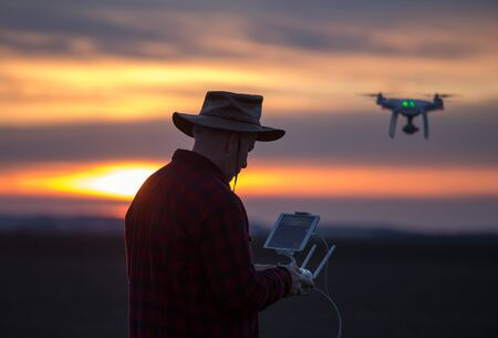 Farmer with hat driving drone above field in winter time Stock fotó