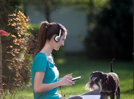 Teenage girl sitting on lawn with headphones and mobile while cute dog making her company