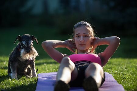 Girl doing crunches on grass in backyard while dog making her company