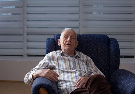 Senior man suffering from dementia sitting on armchair at home